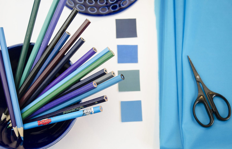 Moodboard Textildesign Assemblage mit Bunstiften, Farbschema, Farbkarten mit Dederon, Schere und blauer Schüssel