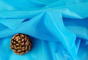 türkisfarbener Dederonstoff in Falten gelegt mit grßer Pinienzapfe